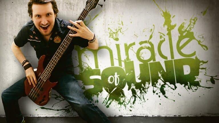 """Gavin Dunne posiert mit seiner E-Gitarre vor dem Schriftzug """"Miracle of Sound"""""""