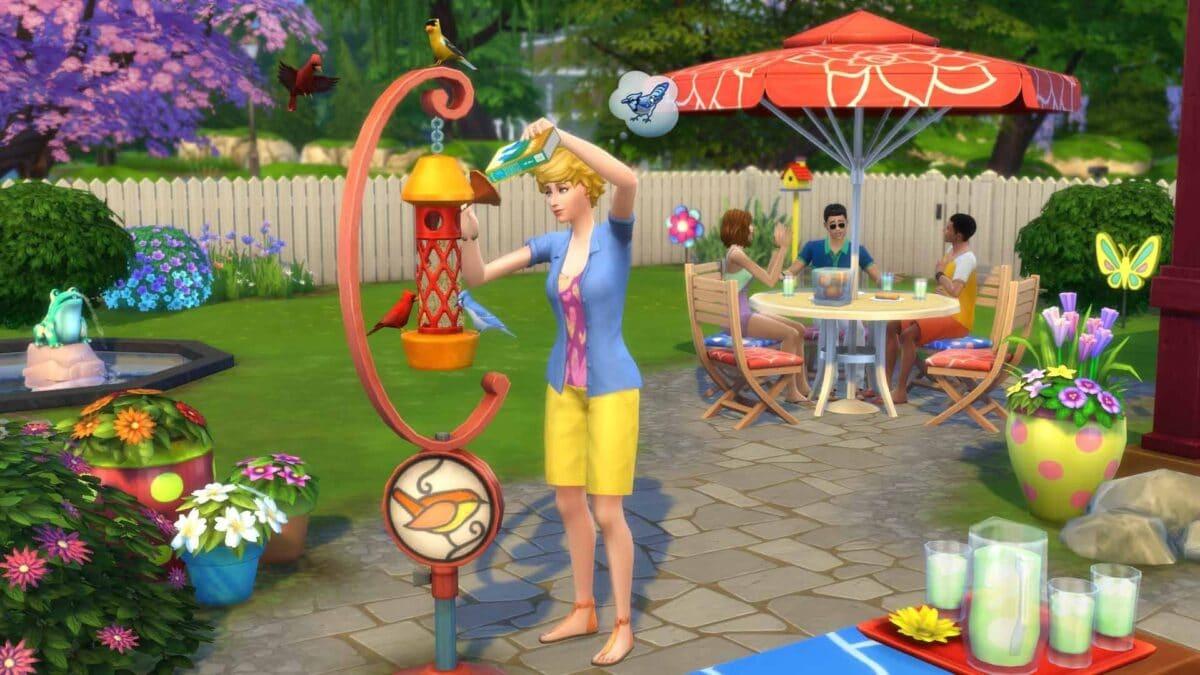 Simfrau füttert Vögel an Vogelhaus in Garten