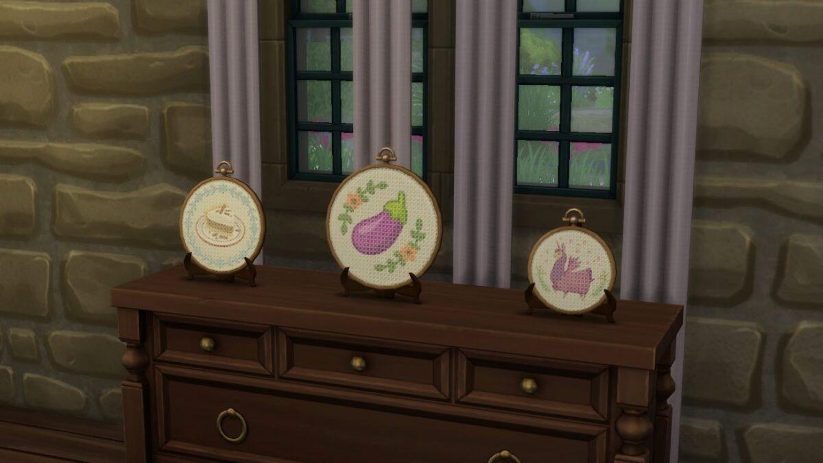 Sims 4 Landhaus-Leben Guide Drei unterschiedlich große Stickarbeiten auf einer Kommode ausgestellt