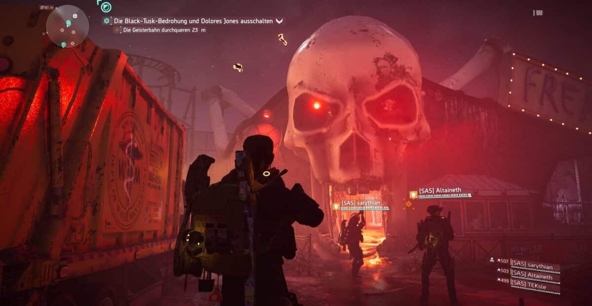Ein Vier-Agenten-Team steht vor dem als riesigem Skelettschädel geformten Eingang einer Vergnügungspark-Geisterbahn.