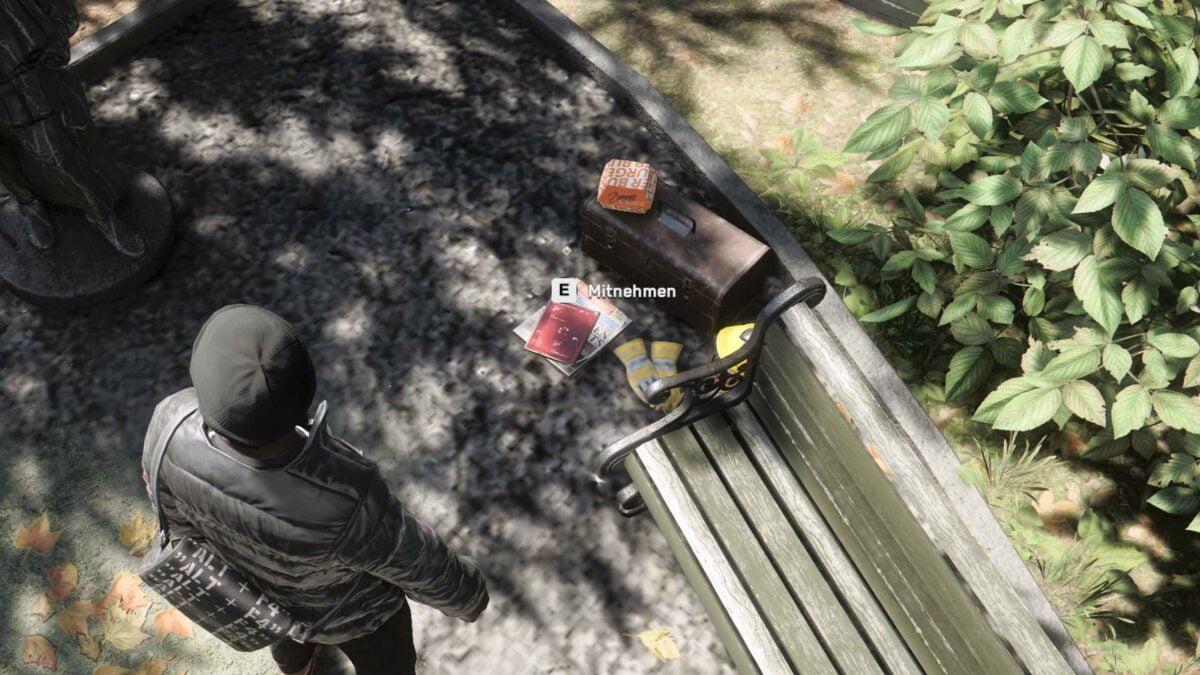 Watch Dogs Legion Agent steht in Park vor Textdatei in Form herumliegender Zeitschrift